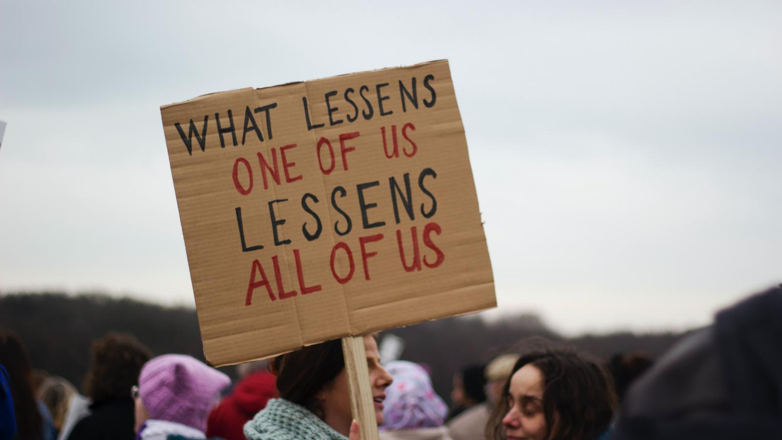 "Protesting woman holding up a sign saying ""what lessens one of us, lessens all of us"" - credit Micheile Henderson"